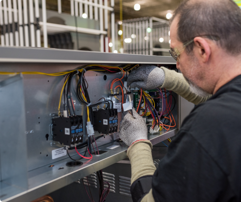 A man working on some wires for a product at Rheem