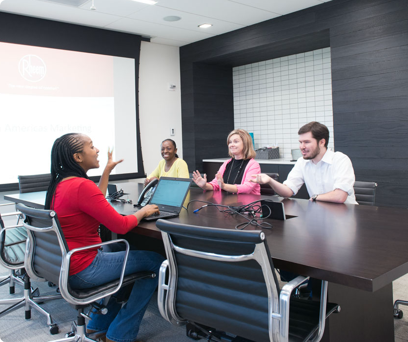 A diverse group of four people at a desk in a conference room smiling at Rheem